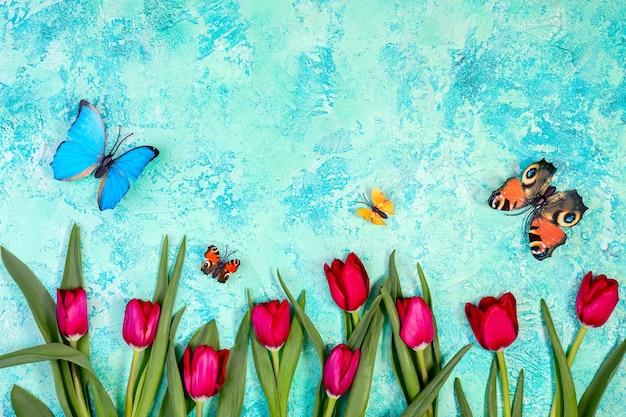 Tulipani rossi e farfalle svolazzanti su uno sfondo strutturato azzurro e verde con spazio di copia