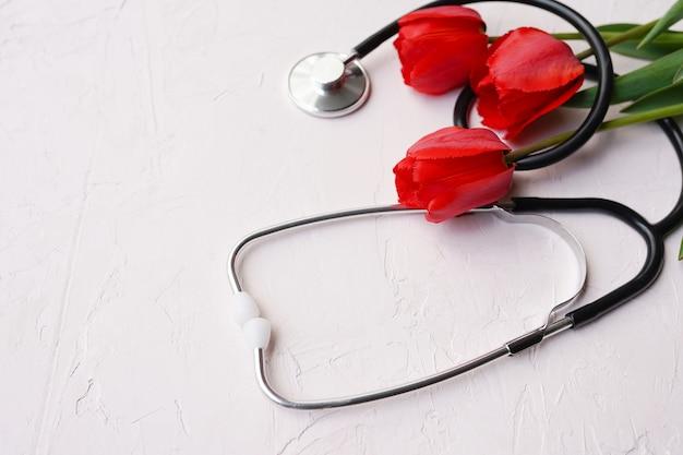 Tulipani rossi e stetoscopio su sfondo bianco. giornata del dottore nazionale. felice giorno dell'infermiera.