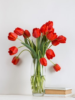 Tulipani rossi in un vaso, libri e materiale scolastico su bianco.