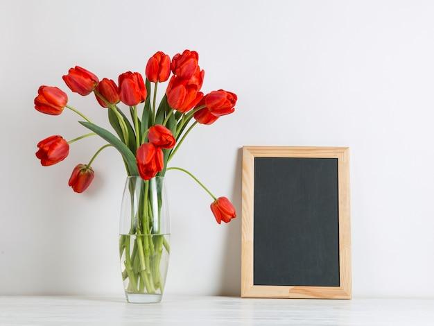 Tulipani rossi in un vaso e lavagna sul tavolo su bianco copia spazio.