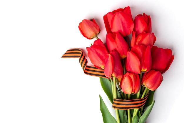 Tulipani rossi con nastro di san giorgio su sfondo bianco. giorno della vittoria o giorno del difensore della patria.