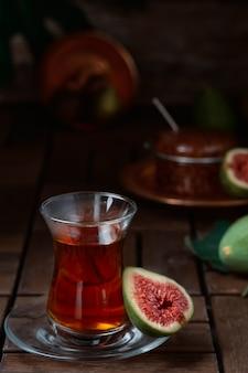 Tè rosso turco in un tradizionale bicchiere armudu, mezzo fico maturo accanto