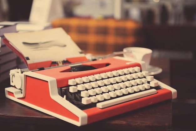 Macchina da scrivere rossa con foglio di carta su tavola di legno