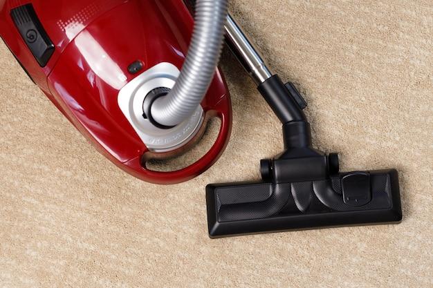 Aspirapolvere rosso su un tappeto beige