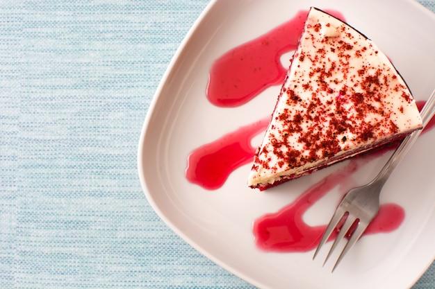 Fetta di torta di velluto rosso su sfondo blu vista dall'alto