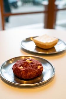 Biscotto di velluto rosso con noce di macadamia sul piatto