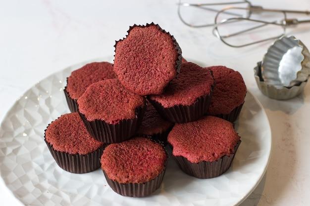 Cupcake di velluto rosso in forma per la cottura su un tavolo bianco