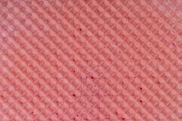 Reticolo di struttura della cialda rossa, primo piano, vista dall'alto. sfondo di superficie strutturata wafer rosa