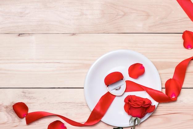 Decorazione di nozze rossa con anelli e rose.