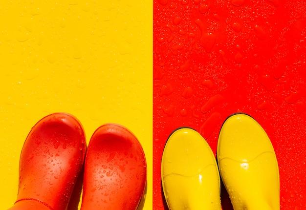 Sfondo rosso bagnato con stivali di gomma gialli e sfondo giallo con stivali rossi su di esso