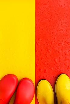 Sfondo rosso bagnato con stivali di gomma gialli e sfondo giallo con stivali rossi