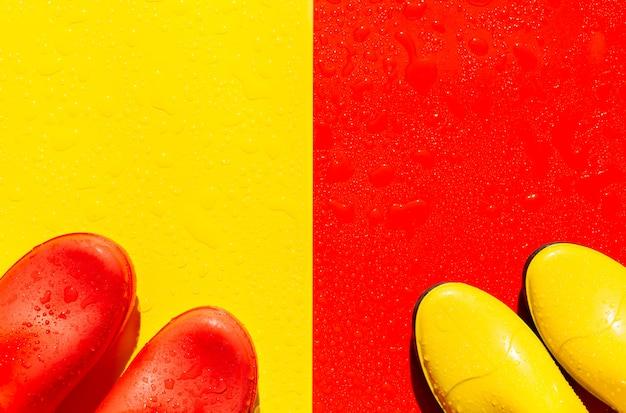 Rosso bagnato con stivali di gomma gialli e giallo con stivali rossi su di esso.