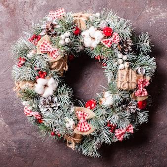 Ghirlanda natalizia rossa e bianca con fiocchi e fiori di cotone