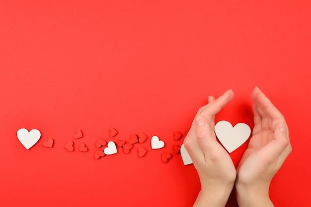 Cuori rossi e bianchi su sfondo rosso. donna che tiene cuore bianco. copia spazio.