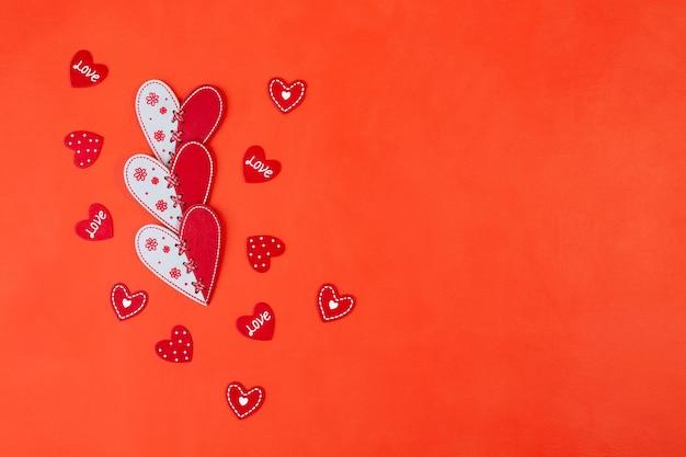 Cuori rossi e bianchi e piccoli san valentino su uno sfondo rosso con uno spazio di copia.vista dall'alto, piatto laici.
