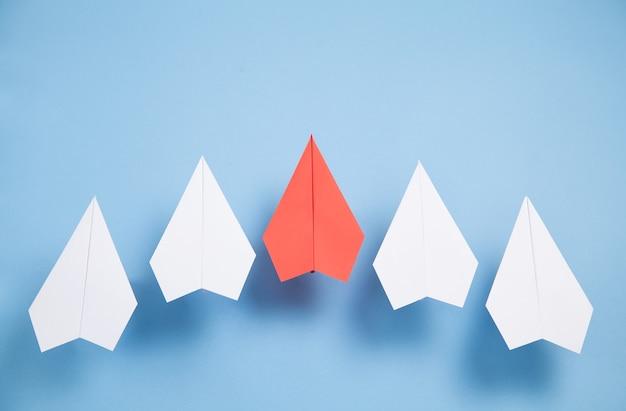 Aeroplani di carta rossi e bianchi su sfondo blu. comando. lavoro di squadra