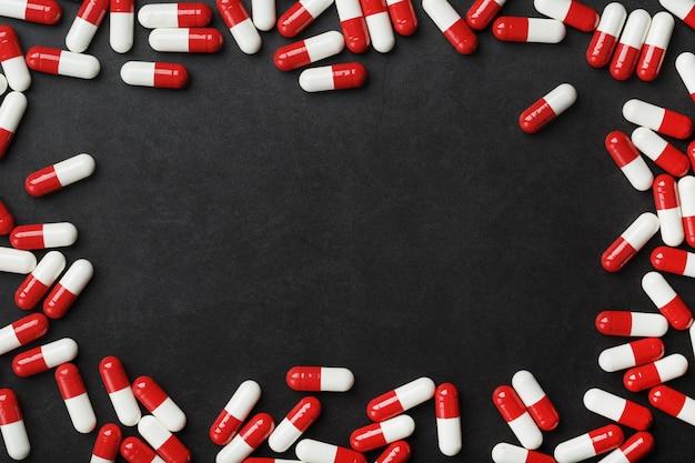 Compresse rosse e bianche sotto forma di cornice con spazio libero su sfondo nero. cornice dell'ampolla, vista dall'alto