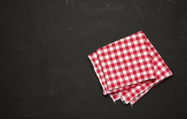 Asciugamano da cucina in tessuto rosso-bianco su un tavolo in legno nero, vista dall'alto, copia dello spazio