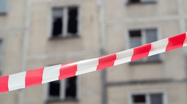 Nastro di avvertimento bianco e rosso che vieta il passaggio alla casa da demolire