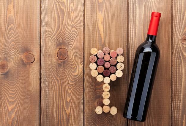 Bottiglia di vino rosso e tappi a forma di vetro. sullo sfondo di un tavolo in legno rustico con spazio per la copia