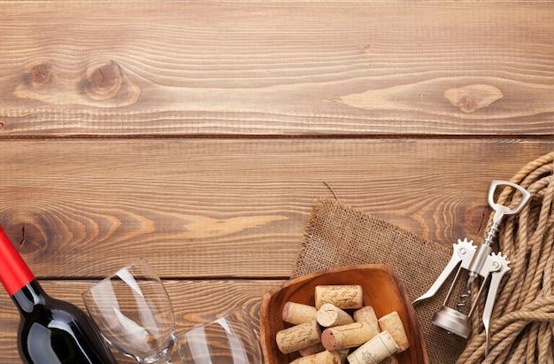 Bottiglia di vino rosso, bicchieri, ciotola con tappi di sughero e cavatappi. vista dall'alto su sfondo tavolo in legno rustico con spazio copia