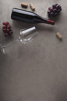 Vino rosso in bottiglia, uva, tappi di sughero e un bicchiere di vino. vista dall'alto. copia spazio del tuo testo.