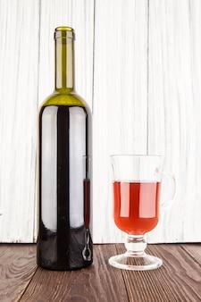Vino rosso e una bottiglia isolata sopra la tavola di legno