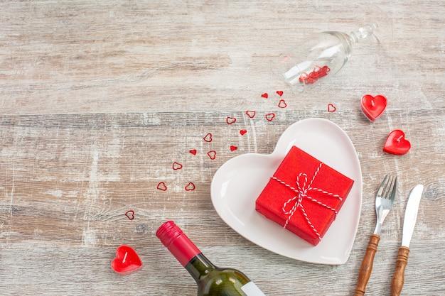 Bottiglia di vino rosso e confezione regalo d'amore, candele, fiori
