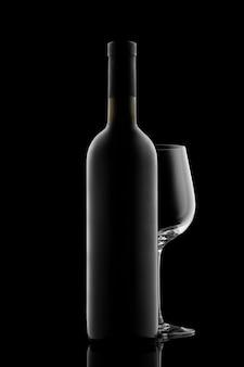 Bottiglia di vino rosso e bicchiere di vino isolato su sfondo nero