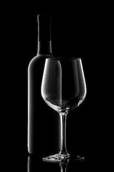 Bottiglia di vino rosso e bicchiere di vino isolati su sfondo nero