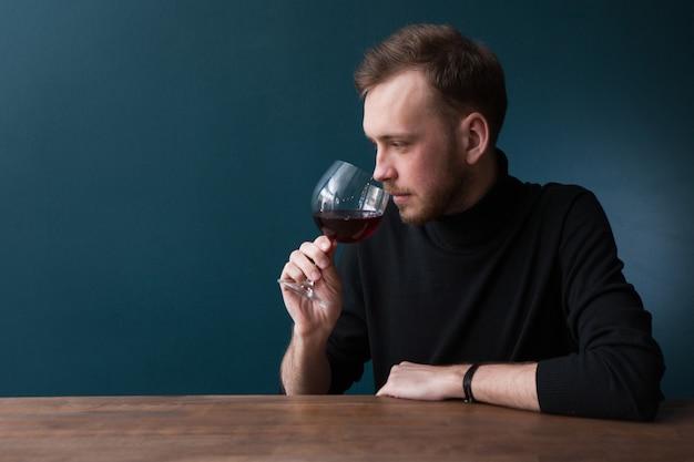 Degustazione di vini rossi. buongustaio maschio. pubblicità di bevande alcoliche, giovane uomo pensieroso al bar su sfondo blu con spazio libero. bevanda squisita, concetto di gusto