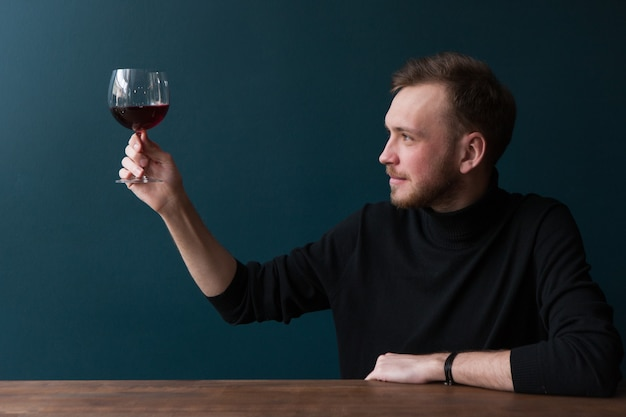 Degustazione di vini rossi. brindisi maschile. pubblicità di bevande alcoliche, giovane interessato al bar su sfondo blu con spazio libero. bevanda squisita, celebrazione della festa, concetto di gusto