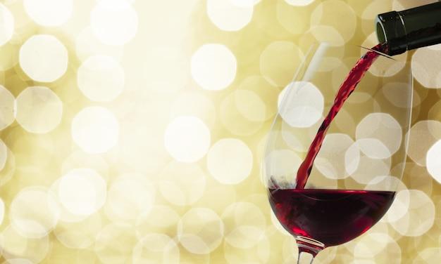 Bicchiere di vino rosso su sfondo bokeh, bevanda alcolica dell'uva.