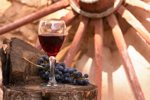 Bicchiere di vino rosso e grappolo d'uva su uno sfondo di legno vecchio.