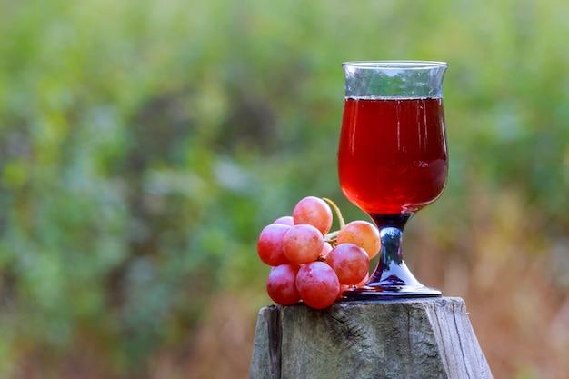 Bicchiere di vino rosso e grappolo d'uva sul tavolo di legno contro la vigna in estate