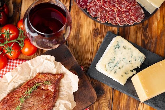 Vetro di vino rosso e blocchi di formaggio sulla tavola di legno si chiuda