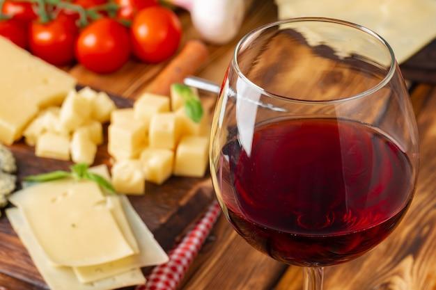 Vetro di vino rosso e blocchi di formaggio sulla tavola di legno
