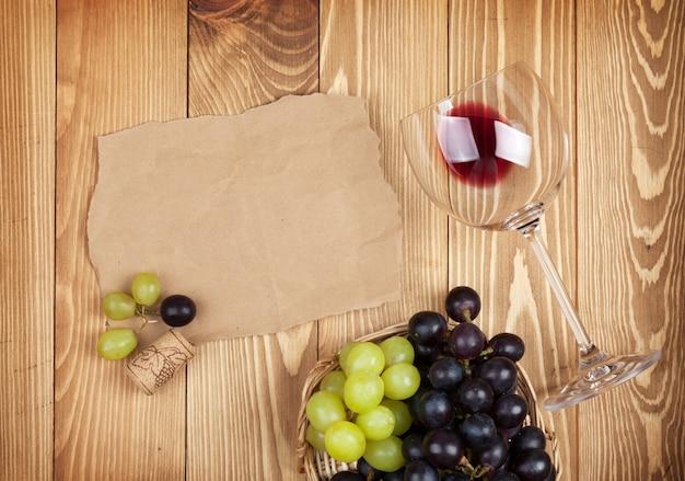 Bicchiere da vino rosso e uva sul fondo della tavola in legno con spazio copia