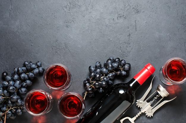 Vino rosso in bicchieri, uva, bottiglia di vino, sfondo cornice cavatappi