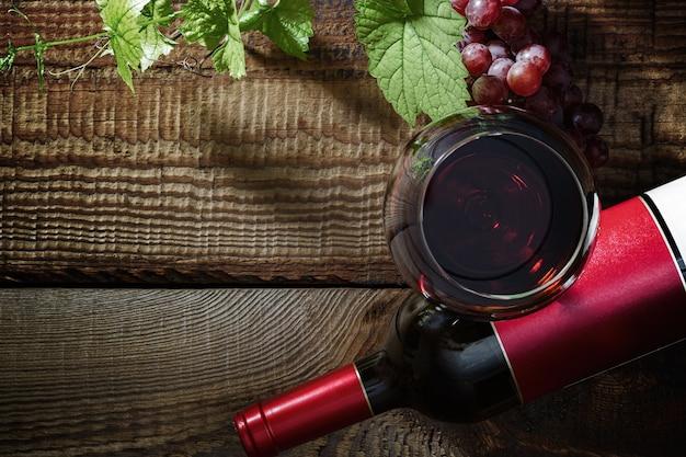 Vino rosso e uva. vino rosso in un bicchiere, bottiglia, uva, foglie di vite su un vecchio tavolo vintage. vista dall'alto.