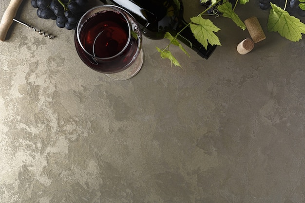 Vino rosso e uva. vino e uva in un ambiente vintage con tappi di sughero su un tavolo di legno. vista dall'alto. copia spazio del tuo testo.