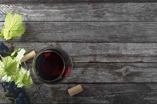 Vino rosso e uva. vino e uva in un ambiente vintage con tappi di sughero su un tavolo di legno. vista dall'alto.