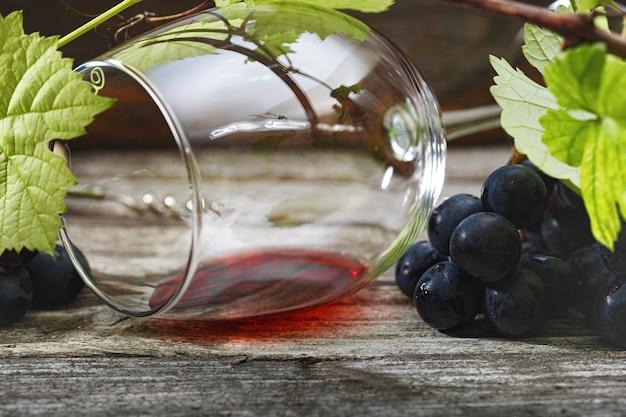 Vino rosso e uva. vino e uva in un ambiente vintage con tappi di sughero su un tavolo di legno.