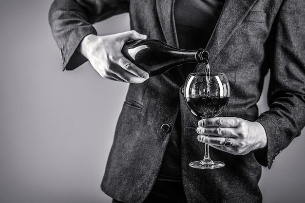 Il vino rosso viene versato dalla bottiglia al bicchiere. bottiglia da bere gourmet, bicchiere da vino rosso, sommelier, degustazione. cameriere che versa vino rosso in un bicchiere. sommelier uomo, degustazione, cantina, enologo maschio