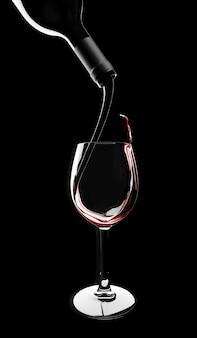 Il vino rosso viene versato dalla bottiglia in un bicchiere sul nero