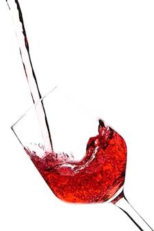 Il vino rosso sta versando in un calice di vetro su uno sfondo bianco. bevande alcoliche. foto di alta qualità