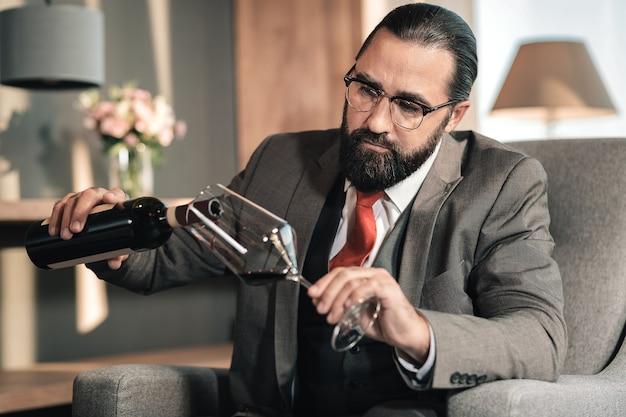 Vino rosso. uomo con gli occhiali e cravatta rossa che versa vino rosso nel bicchiere dopo una lunga giornata faticosa