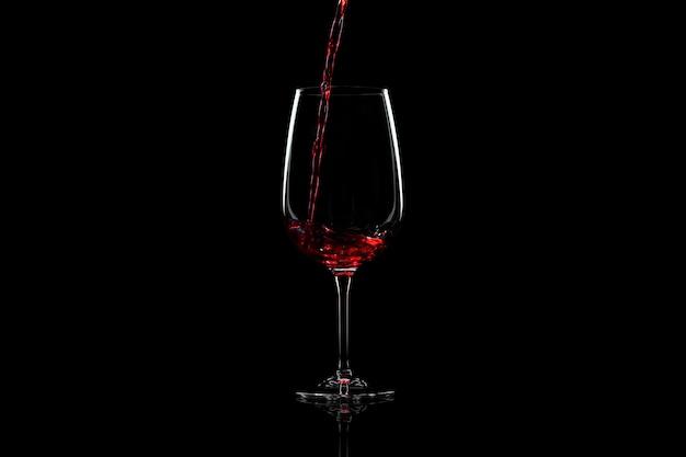 Vino rosso che versa in un bicchiere di vino