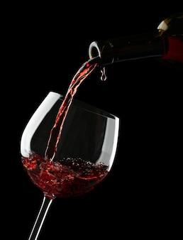 Vino rosso che versa nel bicchiere di vino