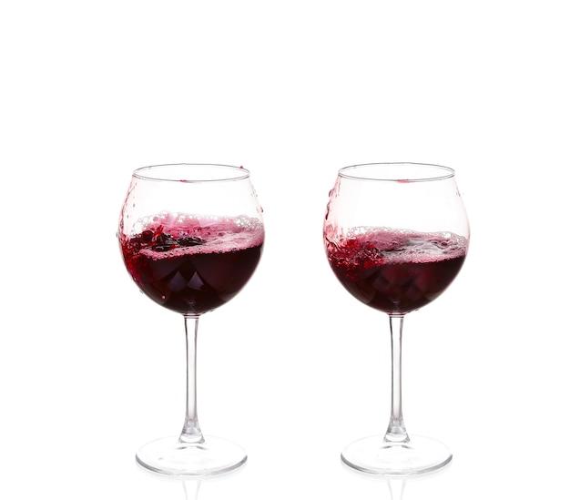Vino rosso che versa su bianco